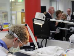 Foreground: A dentistry student hard at work. Background: Dignitaries, including Senator The Hon Gavin Marshall, touring the La Trobe Rural Health School