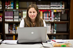Student looking at laptop with books behind