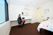 Female student on her laptop within her student accommodation, which consists of a single bed, desk and a chair.