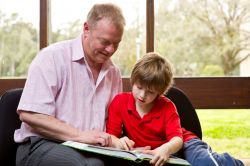 male helping young male child with reading