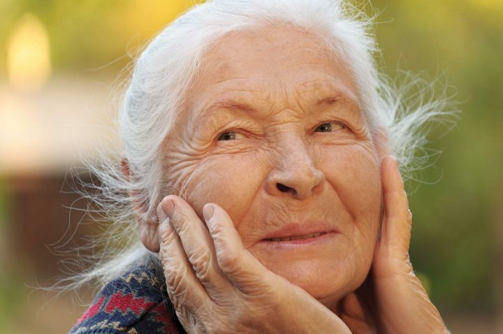 Older woman with hands on face, smiling.
