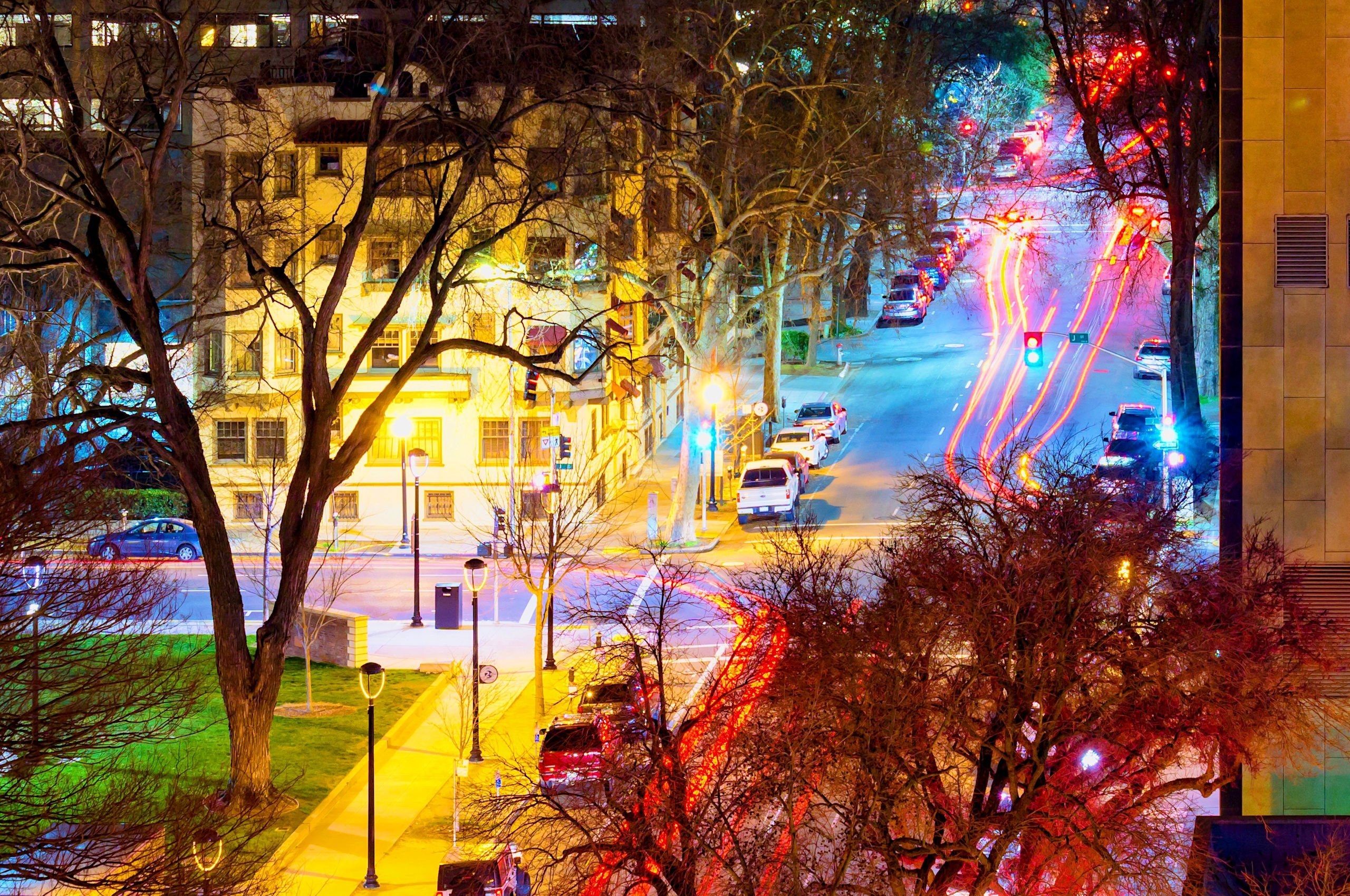 Night-time streetscape showing an intersection with a park, large trees, apartment buildings, skyscraper, parked cars and old-fashioned street lamps, with bright multi-coloured lighting and red trails from car tail-lights