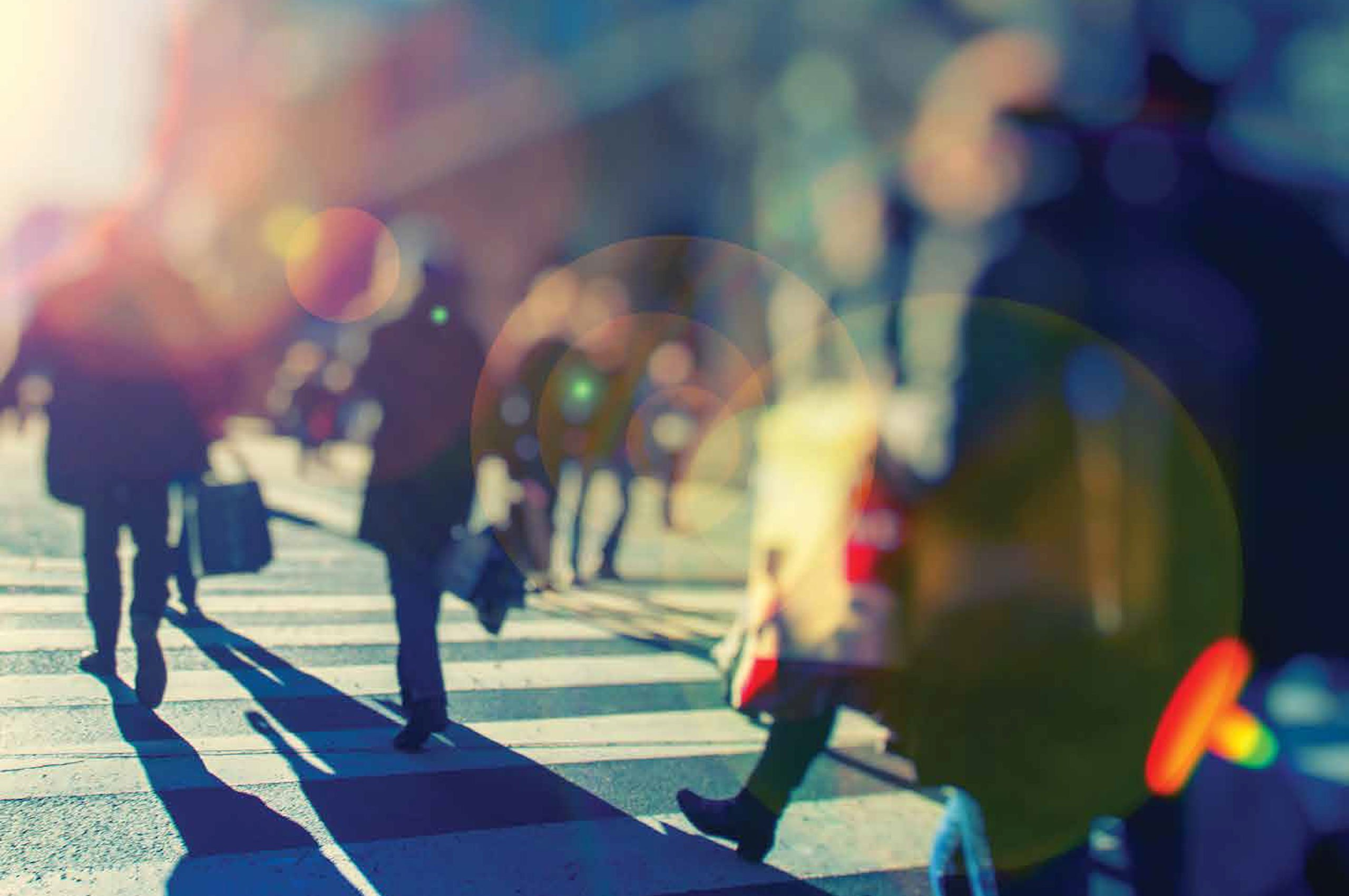 High-contrast, partly blurred image of people walking across a zebra crossing with colourful lens flare