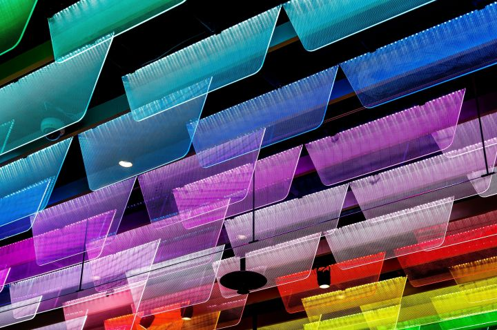 Brightly-lit colourful perspex plates arranged in rainbow order hang from a dark ceiling