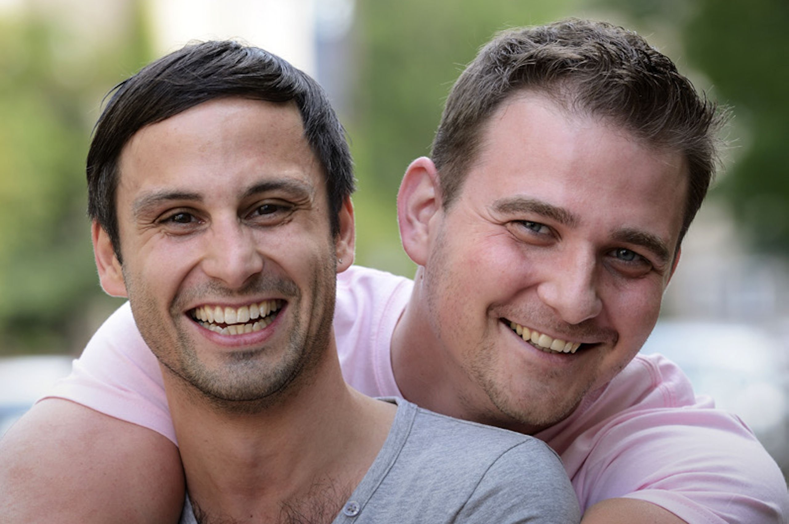 Two masculine people hugging, smiling and looking at the camera