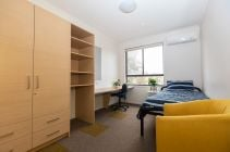 Single bedroom with built-in wardrobe, desk and chair.