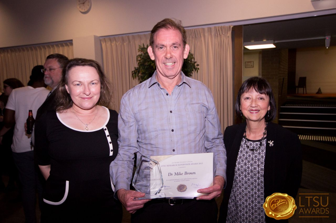 Dr Mike Brown wins the 2015 La Trobe Student Union (LTSU) inaugural Research Supervisor Award, Odeon Theatre La Trobe University Bundoora 15th October 2015.  L to R: Karen O'Reilly Briggs, Dr Mike Brown and Pam Delly. Image courtesy of LTSU.
