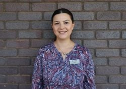 Seher Ozer Ozonal, Associate Lecturer - Student Learning standing in front of brick wall smiling