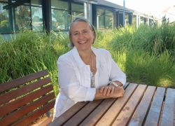 sue hedley, international support officer sitting on wooden bench outside smiling at camera