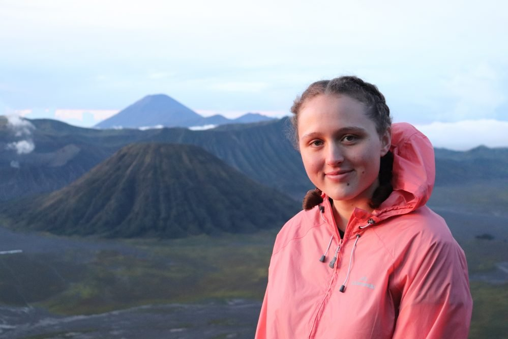 Person standing with volcanoes in the distance.