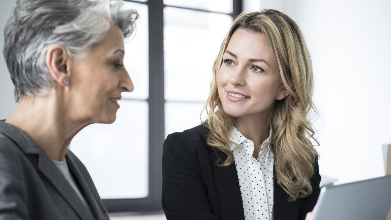 two women in professional clothing discussing